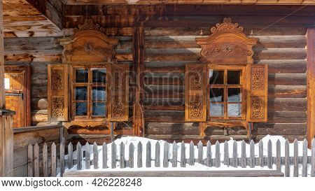 The Old One-storey House Was Built Of Unpainted Logs. There Are Shutters And Carved Decorations On T