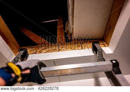 Hand Gripping The Last Rung On A Ladder Leading To An Open Attic
