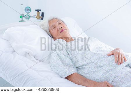 Senior Woman Lying In Bed At Hospital Ward. Medicine, Health Care And People Concept.