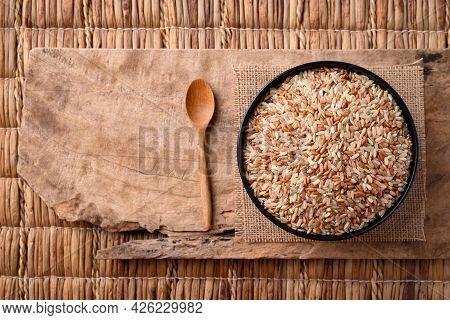 Organic Thai Highland Brown Rice Grain In A Bowl With Spoon On Wooden (cargo Rice, Loonzain Rice Or