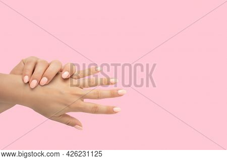 Beautiful Female Hands With Stylish Nail Manicure Gel Polish On Pink Background. Top View Of Groomed