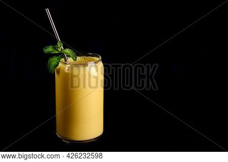Mango Lassi In Glass With Tube On Black Background. Traditional Indian And Pakistan Drink With Yogur