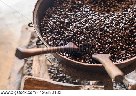 Close-up Of Old Metal Pot Containing Dark Roast Coffee Beans After Roasting. Roasting Brings Out The