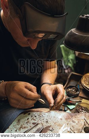 The Jeweler Repairs Gold Jewelry In His Workshop, Examines The Ring For Defects