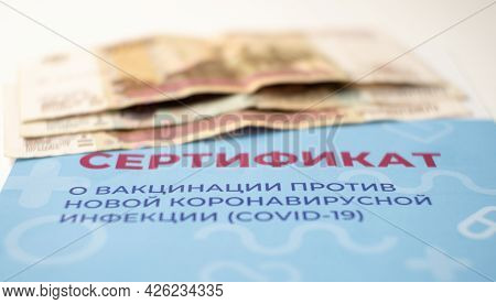 Close-up Of The Vaccination Certificate And Money. Sale Of Fake Forms By Scammers. Selective Focus.