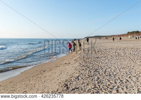 Few Of People Walking On The Beach In Spring.