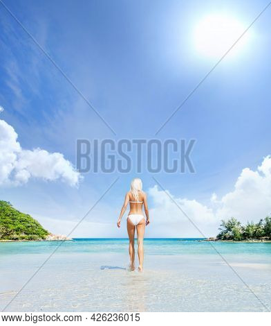 Beautiful, Young And Happy Blond Woman Walking On The Beach In White Swimsuit. Fit And Sexy Fashion