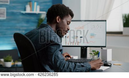 Selective Focus On Black American Guy Working From Home, Taking Notes On Notepad While Remote Workin