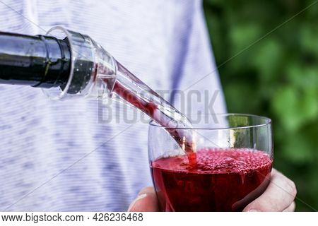 The Winemaker Pours Wine From A Bottle Into A Glass Through An Aerator Against The Background Of Gra