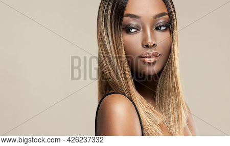 Beautiful African American Woman With Dyed And Straight Hair. The Beauty Of An Afro Black Girl With