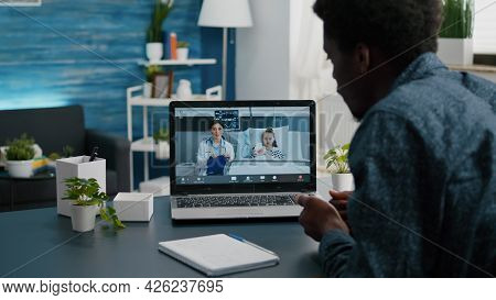 African American Dad On Internet Video Call Using Laptop, Talking With Doctor From Hospital Ward Abo