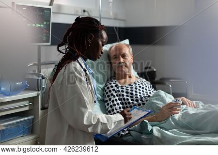 African American Doctor In Hospital Room Discussing Diagnosis And Treatment With Sick Senior Man Lay