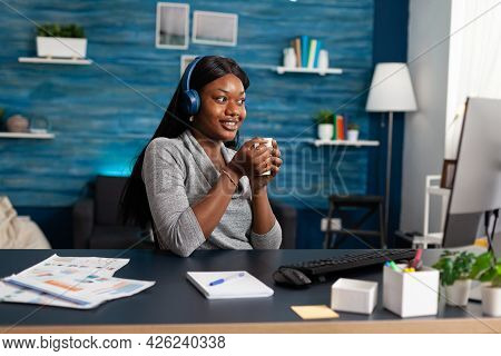 African American Student Holding Cup Of Coffee In Hands Wearing Headphones While Listening Modern Mu