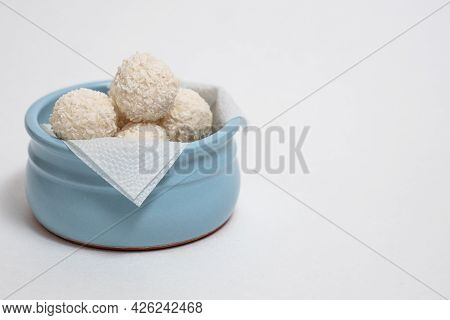 Round Coconut Candies In A Blue Bowl On A White Background Isolate, Coconut Balls, Homemade Vegetari