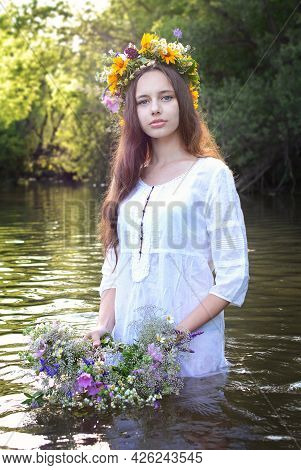 Portrait Of A Young Beautiful Girl In White With A Wreath On Her Head Against The Background Of The