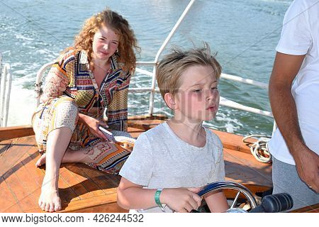 A Boy With A Concentrated Look Controls The Ship At Sea.