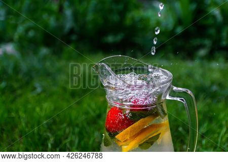 Defocus Jet Splash Spray Water Bubbles In Glass Jug Of Lemonade With Lemon, Strawberry And Mint On N