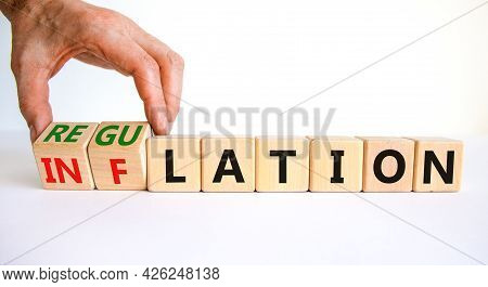 Inflation Or Regulation Symbol. Businessman Turns Cubes And Changes The Word Inflation To Regulation