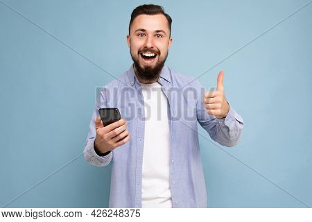 Photo Shot Of Positive Handsome Bearded Good Looking Young Man Wearing Casual Stylish Outfit Poising