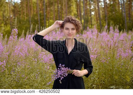 Young Woman With A Bouquet Of Lupines In Her Hand Against The Background Of Blooming Ivan-tea. Soft