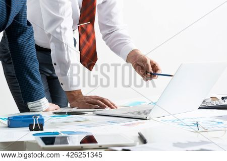 Businessman And Businesswoman Stand Near Desk With Financial Annual Report. Business People Meeting