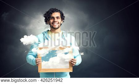 Man holding frame with blue sky and clouds . Mixed media