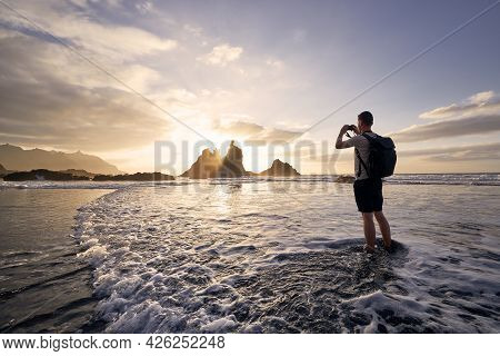 Man During Photographing Landscape With Cliff. Young Photographer On Beach At Beautiful Sunset. Tene