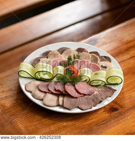 Platter With Cold Cuts, Thin Slices Of Meat, Ham And Cucumber Rolls On Wooden Table. Soft Focus. Cop