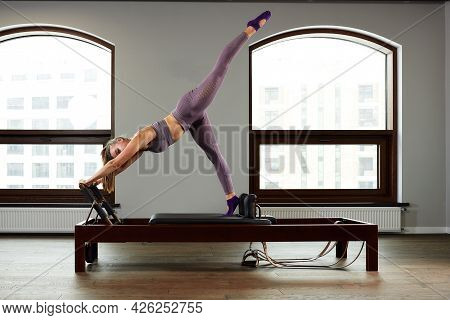 Girl Instructor On Reformer Cadillac, Posing, Showing Exercises For Spine Correction, Modern Reforme
