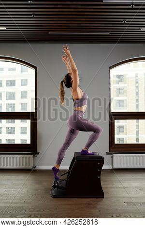 A Woman Yoga Instructor Trains On A Reformer Barrel Against The Window, Correction Of The Musculoske