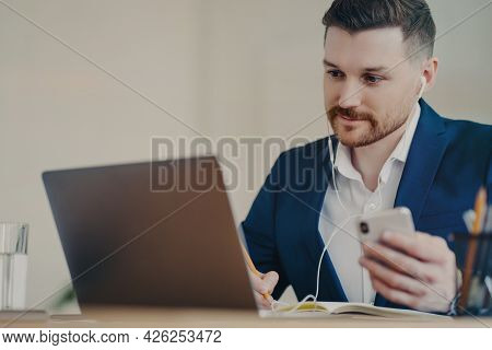 Focused Male Director Wearing Corporate Clothing In Wireless Earphones With Cellphone In Hand Watchi