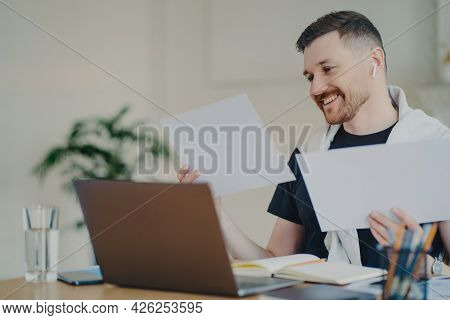 Positive Young Businessman In Casual Wear Analyzing Project Results And Feeling Happy, Using Modern