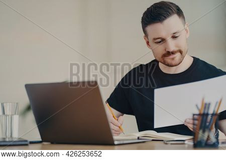 Skilled Professional Male Expert Busy Doing Paper Report Edits Online Files Via Laptop Works At Desk