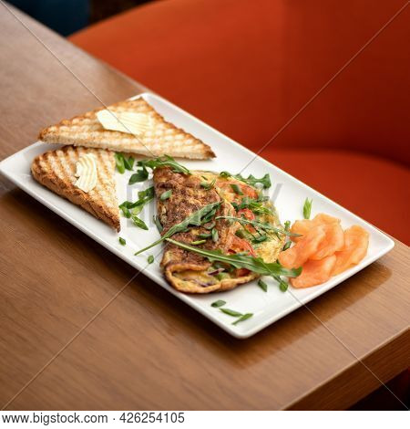 Slices Of Red Fish, Omelet With Arugula And Toast With Butter On White Platter. Morning Mood, Breakf