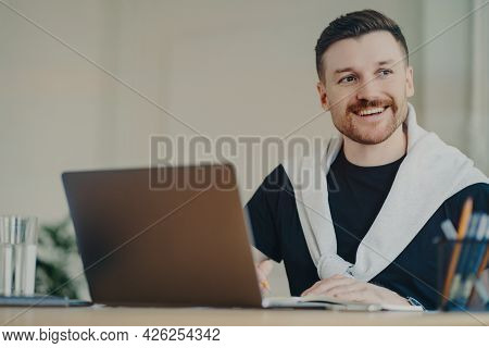 Happy Bearded Man Office Worker Writes Organisation Plan Works Remotely Makes Notes Of Info Sits In