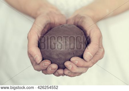 Womens Hands Holding A Grey Ball. Prepare To Work In A Pottery Workshop. Pottery Made Of Clay With T