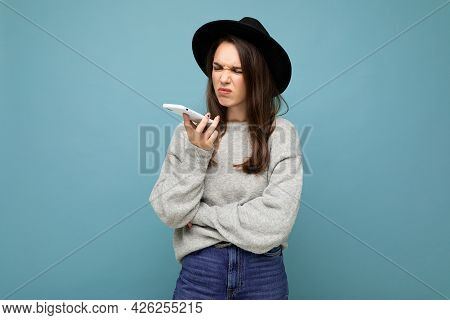 Young Asking Dissatisfied Brunette Woman Wearing Black Hat And Grey Sweater Holding Smartphone Looki