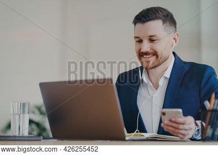 Happy Male Office Worker Uses Modern Technologies Poses At Desktop Holds Mobile Phone Makes Video Ca