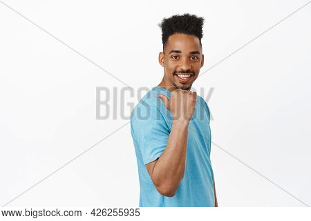 Handsome Young Male Model Model, African American Guy In T-shirt Pointing Finger Left, Behind His Sh