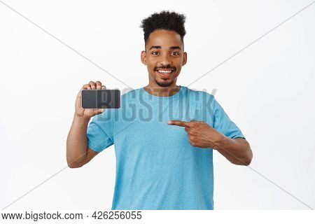 Cheerful African American Male Model Pointing Finger At Horizontal Mobile Phone Screen, Recommending