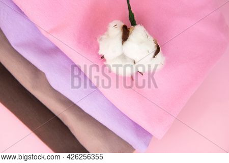 Colorful Cotton Folded Clothes Stack. And Sprig Of Cotton. Stack Of Multicolored Clothes On Pink Bac