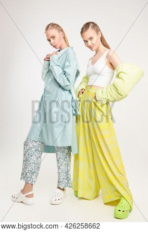 Romantic summer style. Two beautiful fashion models girls pose in elegant summer clothes and clogs. Full length studio portrait on a white background. Fashion.