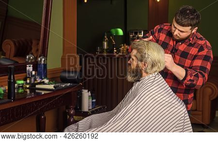Guy With Long Dyed Blond Hair. Professional Hairstylist In Barbershop Interior. Hipster Client Getti