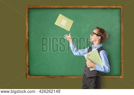 Caucasian Schoolboy Teen In Classroom Amid School Board With Notebooks In Hand. One Notebook The Boy