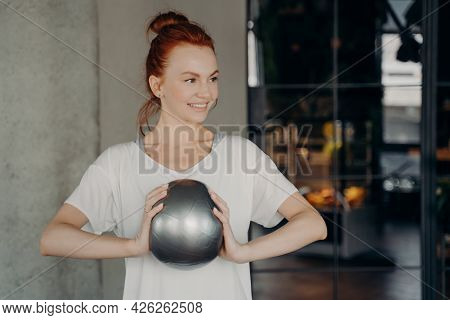 Sportive Good Looking Woman With Red Hair Wearing Sports Clothes Holding Small Fitball With Two Hand
