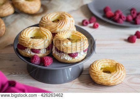 Cream Puff Rings Eclairs Choux Decorated With Fresh Raspberries On Grey Plate, Selective Focus