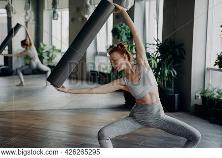 Young Beautiful Slim Woman With Red Hair In Bun Training In Fitness Studio, Holding Pilates Foam Rol