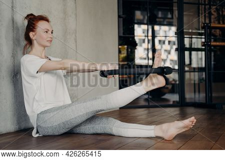 Side View Of Beautiful Motivated Fit Female Sitting On Floor In Fitness Studio And Using Black Pilat