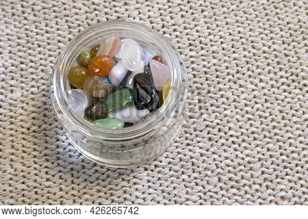 Collection Of Semi-precious Gemstones In Small Glass Jar On Blurred Grey Knitted Background Close Up
