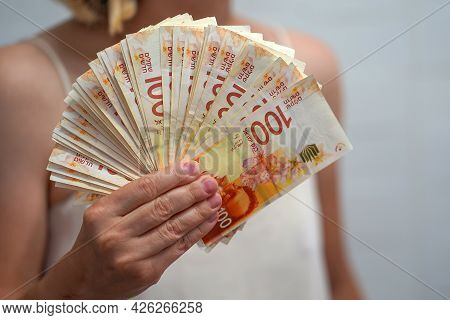 In The Hands Of A Lot Israeli Money, Denominations Of 100 Sheqel. Woman Hands Hold Fan Of New Israel